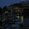 The marina after dark, lights reflected in the water.
