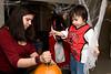 One year old Lashaun Enosse watches family friend Leah Etherington carve a pumpkin