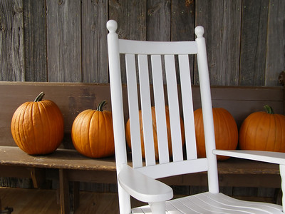 Front porch with rocking chair and pumpkins