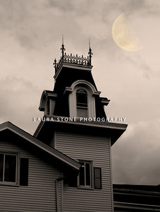 Spooky-looking house in sepia tones. Moon in distance.