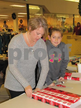 Tracy and Elizabeth Gailey volunteer wrapping gifts at the St. Ed's French club booth.  The French club is raising money for their trip to France in 2014.