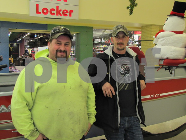 Patrick Straw and Ray Wojcinski look over one of the fishing boats on display at the Crossroads Mall.