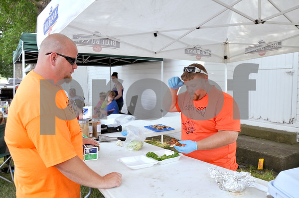 "-Messenger photo by Joe Sutter<br /> <br /> Ricky Cofer, left, watches his teammate Nate Nostrom arrange some smoked chicken on a bed of lettuce for optimal visual presentation. The ""Fat Boys BBQ"" team was one of seven competing at the cookoff for the the Humboldt Sesquicentennial celebration Sunday."