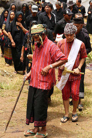 The first person is the ceremony leader. Red is the color of death in Sulawesi.