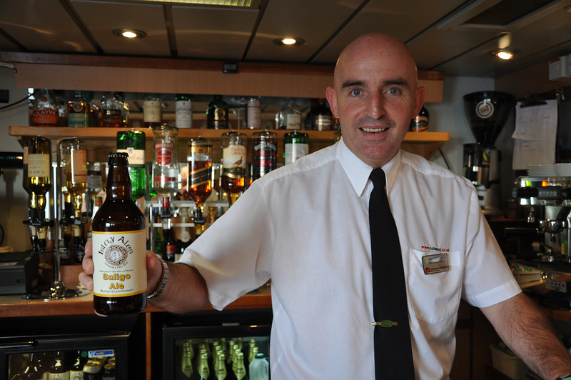Onboard the Macbraynes ferry from Oban to Islay: The friendly barman holds up a bottle of Saligo Ale from the Islay Brewery.