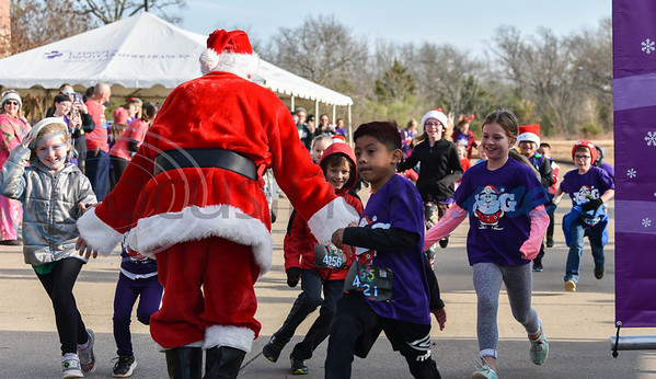 Santa cheers on children as they race across the finish line of the Kids Fun Run on Saturday. The event was part of the 3rd annual Jacksonville Jingle Jog hosted by CHRISTUS Mother Frances. (Jessica T. Payne/Tyler Morning Telegraph)