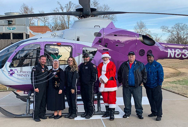 Santa smiles for a photo with CHRISTUS Mother Frances employees after arriving by helicopter at the 3rd annual Jacksonville Jingle Jog sponsored by the hospital. (Jessica T. Payne/Tyler Morning Telegraph)