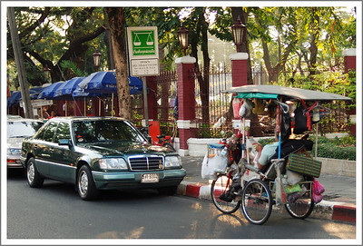 We notice a great variety of vehicles.  I am not sure, but this tricycle seems to be this man's home.