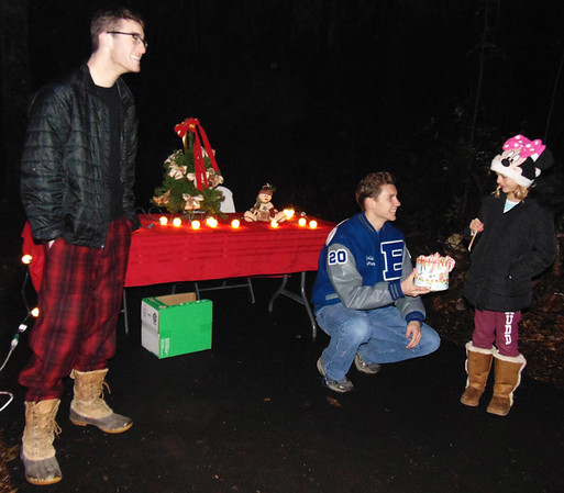Debbie Blank | The Herald-Tribune<br /> At the end of the Festival of Lights, which covered about one-fourth of the paved trail, Kenzi Lacey (from right), 7, was given a candy cane by KSLA members Charlie Laymon and Mason Enneking.
