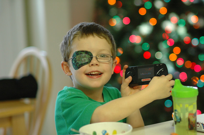 A bowl of cereal, a hand-held toy and a bunch of Christmas presents under the tree waiting to be opened. For a little boy, it does not get much better than that.