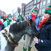 Lowell City of Lights parade. From left, Andy Monaco, 10, of Littleton, Addie Ratta, 11, of Littleton, Ashley Booth, 17, of Chelmsford, and Sophie Miller, 12, of Belmont, with Shetland pony Ringo. All are with the Littleton Hack 'n' Tack group, waiting on Jackson Street. (SUN/Julia Malakie)