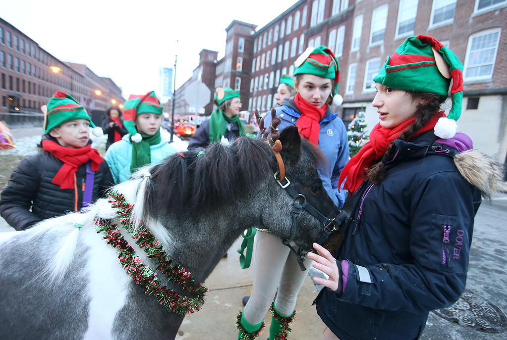 . Lowell City of Lights parade. From left, Andy Monaco, 10, of Littleton, Addie Ratta, 11, of Littleton, Ashley Booth, 17, of Chelmsford, and Sophie Miller, 12, of Belmont, with Shetland pony Ringo. All are with the Littleton Hack \'n\' Tack group, waiting on Jackson Street. (SUN/Julia Malakie)