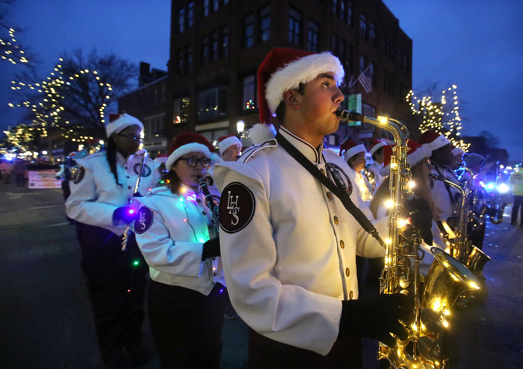 . Lowell High senior Austin Silva on saxophone with marching band in Lowell City of Lights parade. (SUN/Julia Malakie)