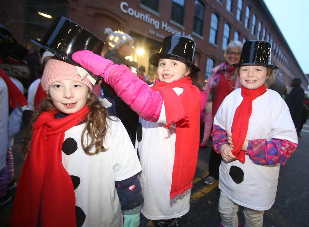 . Lowell City of Lights parade. From left, Sienna Lefevbre, Morgan Yost, and Chloe McGrath, all 7 and from Lowell, with Girls Scout Troop 62409, in staging area on Jackson Street. (SUN/Julia Malakie)