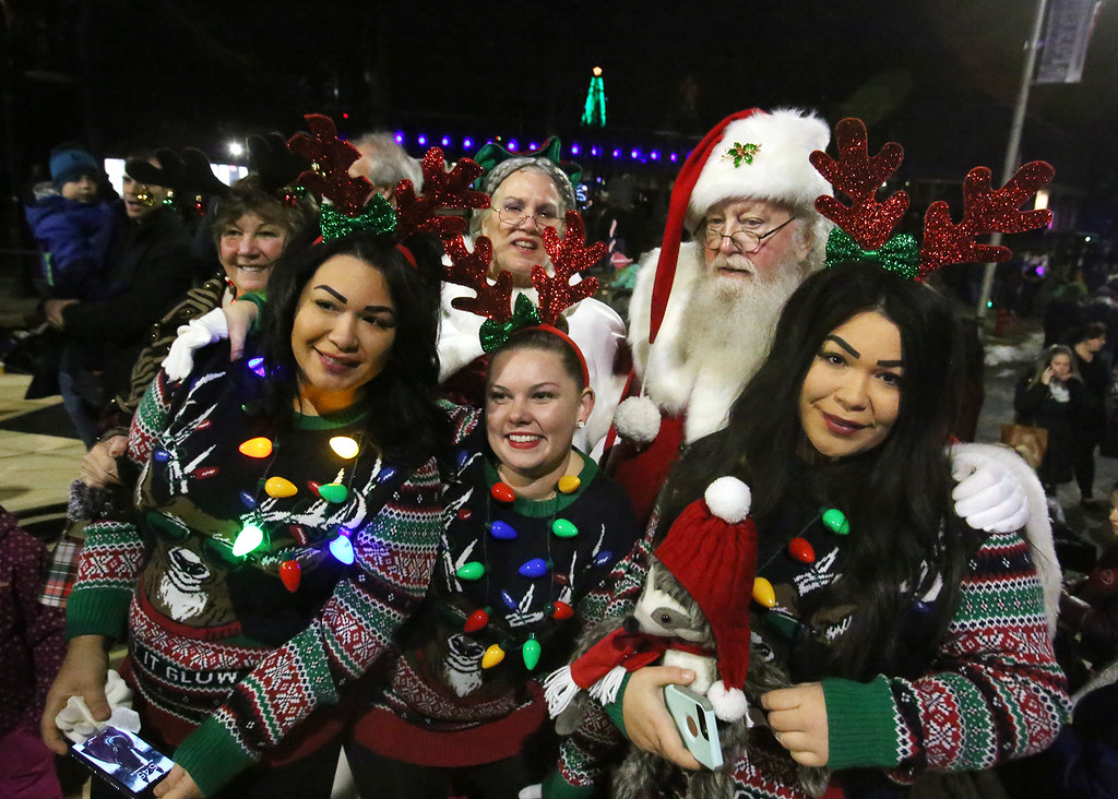 . Lowell City of Lights parade. From left, city councilor Rita Mercier and her granddaughters (all sisters), Sylvia Rivera, Jacklyn Lutkus of Lowell, and Olivia Rivera (Sylvia\'s twin) with Santa and Mrs. Claus. (SUN/Julia Malakie)