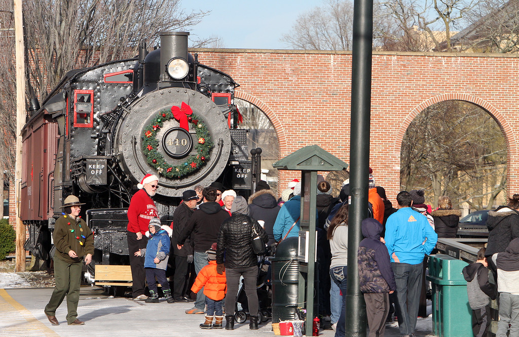 . People by the train engine at the Visitors Center  in downtown Lowell ahead of the City of Lights parade. (SUN/Julia Malakie)