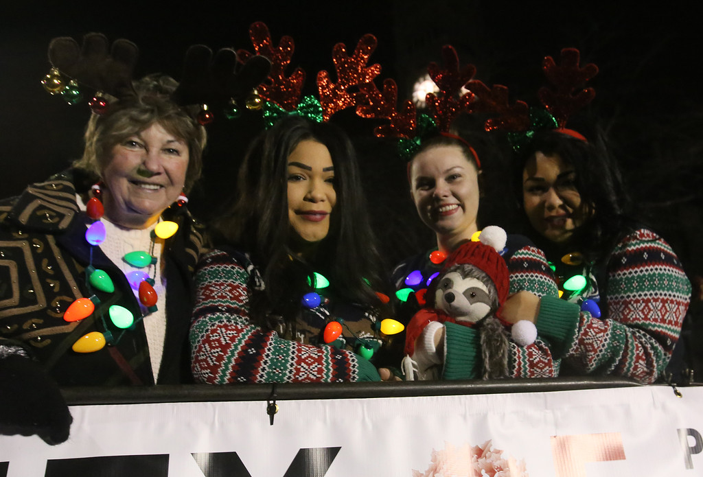 . Lowell City of Lights parade. From left, city councilor Rita Mercier and her granddaughters (all sisters), Olivia Rivera of Dracut, Jacklyn Lutkus of Lowell, and Sylvia Rivera (Olivia\'s twin), at City Hall reviewing stand. (SUN/Julia Malakie)