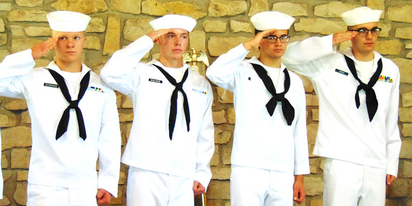 The U.S. Naval Sea Cadets Flying Tigers salute as the flags are brought into the ceremony by fellow members.