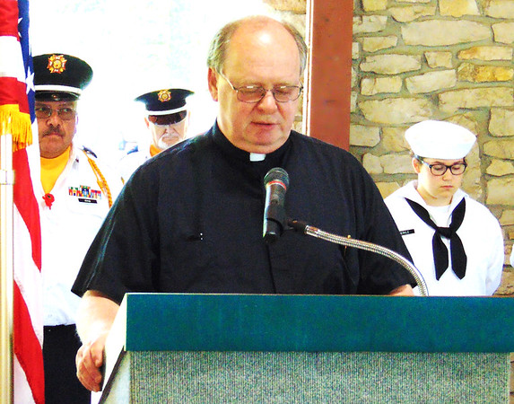 "Debbie Blank | The Herald-Tribune<br /> The Rev. Stan Pondo of St. Louis Catholic Church presented opening and closing prayers. He said, in part, ""Make us truly grateful for the gifts they have given us with their service, their lives."""