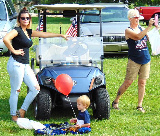 Debbie Blank | The Herald-Tribune<br /> Pat Hill (right) enjoys the parade with her granddaughter, Samantha Baston (left), her son Keaton (on ground), 2, and his cousin Liam Brabender, 2 (in golf cart). All live in Milan.