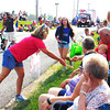 Debbie Blank | The Herald-Tribune<br /> George's Pharmacy employees were among several groups distributing treats to spectators.