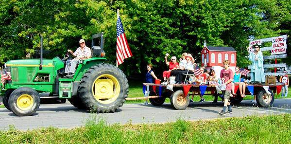 Debbie Blank | The Herald-Tribune<br /> In the Milan Lions Club Fourth of July Parade, the Statue of Liberty, a church and -- of course -- many flag wavers were on the St. Charles Catholic Church float.