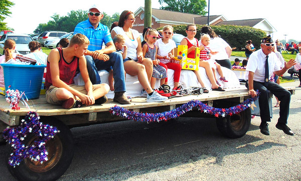 Debbie Blank | The Herald-Tribune<br /> A Legionnaire waves to the crowd as others on the float prepare to throw candy.