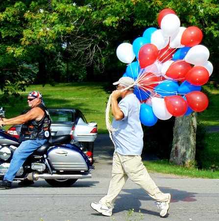 Debbie Blank | The Herald-Tribune<br /> A patriotic man was passing out balloons to young parade spectators.