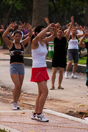 People practicing aerobics in open air. All activities in the park end at about 7 am.