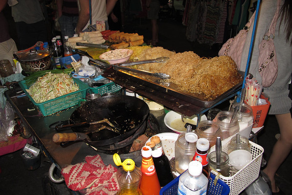 Street food vendor selling Pad Thai and spring rolls. For Pad Thai you pick the type of noodles and meat. The cook will mix them with some vegetables and sauces, probably soy sauce mixed with something else. Very good and takes only a few minutes to be cooked.