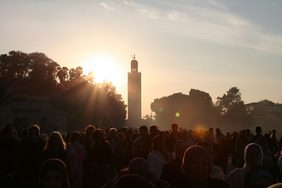 The sun setting in Marrakech with the silhouette of the tower of the Koutoubia Mosque and the crowds in the Place Djemma El-Fna' in Marrakech.