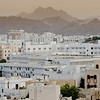 Muscat. White houses, hazy skies and rugged mountain.