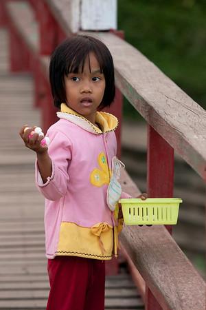 Kid throwing fish food.