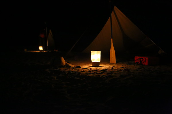 With candles near the tents and improvised toilet.
