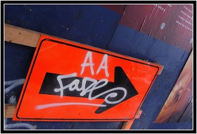 AAFade - this way Almost every flat surface is covered or written on, postered or decayed. Pedestrian signs in New York are no stranger to graffiti's touch.  This blue wall is a temporary work covering to route pedestrians away from work, but already people had pasted six posters up there and two taggers had already put there mark on the surroundings! I picked this sign because I really liked the way that the E from fade follows the arrow through and fills up the arrow's head with a swirl. Having checked with street crimes graffiti directory, there appears to be no AA FADE and only one FADE  listed for New York and not for Manhattan. Obviously not particularly clever or famous then!
