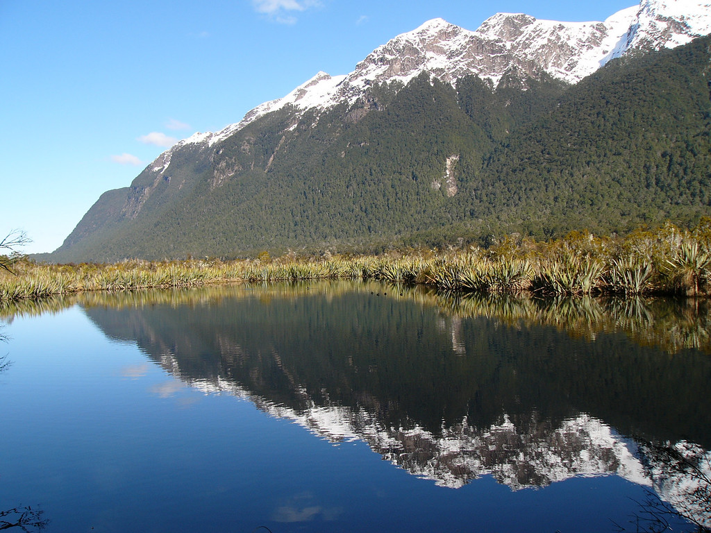 """Mountain reflection. One of the bus stops on the way from Queenstown to Milford Sound. The """"Lord of the Rings"""" was filmed in New Zealand, mostly on the South Island around Queenstown, as far as I can gather. It is possible to go on """"Lord of the Rings"""" horseback and boat rides to visit film set locations. The director, Peter Jackson, is now a New Zealand national hero."""