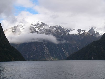 Milford Sound is actually a fjord, cut out by ancient glaciers. It is a day-trip from Queenstown by bus. The 'Milford track' is a popular walking track which takes several days (I think) to complete.