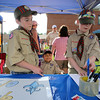 4th of July celebration at Pelham Elementary School. David Kupcho, 10, left, explains how to record sales of pulled pork sandwiches at Cub Scout Pack 610 to fellow scout Austin Murphy, 10. At rear is Callan Nale, 10. (SUN/Julia Malakie)