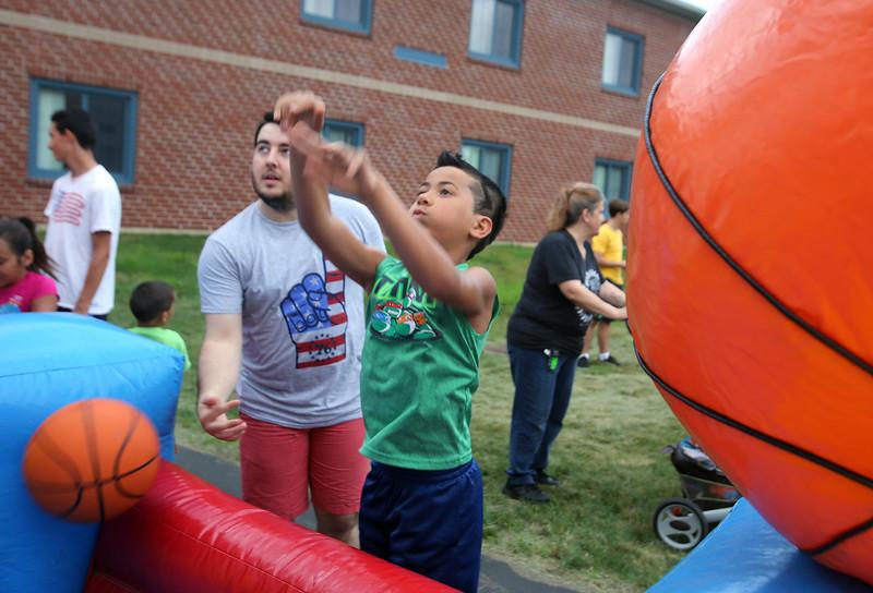4th of July celebration at Pelham Elementary School. Cameron Cruz, 8, of Methuen, tries to make baskets at activity run by Todd Spain of Pelham, with Crossroads Church. (SUN/Julia Malakie)