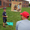 4th of July celebration at Pelham Elementary School. Kevin Hardy, 9, of Pelham, guesses the speed of his next pitch, being measured by Mike Chandonnet of Pelham, with a radar gun. (SUN/Julia Malakie)