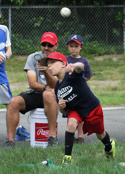 4th of July celebration at Pelham Elementary School. Kevin Hardy, 9, of Pelham, has the speed of his pitches measured by Mike Chandonnet of Pelham, with a radar gun, as Chandonnet's son Joshua, 5, watches. (SUN/Julia Malakie)
