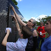 The Moving Wall replica of the Vietnam Veterans Memorial comes to Pelham Village Green for Memorial Day weekend. From left, Peter Costarakis, 12, of Dracut, looks for a name with Sherri Todd of Fremont, N.H., and  Leona Wentworth of Methuen. It turned out he was looking on the wrong half of the wall. (SUN/Julia Malakie)