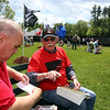 The Moving Wall replica of the Vietnam Veterans Memorial comes to Pelham Village Green for Memorial Day weekend. Ron Normandin of Pelham, left, gets help from volunteer Richard Moore of Pelham, who had custody of a Vietnam Veterans Memorial Directory of Names book, in finding the name of a fellow Normandin grew up with. (SUN/Julia Malakie)