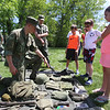 The Moving Wall replica of the Vietnam Veterans Memorial comes to Pelham Village Green for Memorial Day weekend. USMC LCP Tyler Wilkins of Epping, N.H., left, shows a set of Vietnam era field equipment for one soldier to siblings, from left, Josh, 7, Zach, 11, and Abby Chandonnet, 9, of Pelham. (SUN/Julia Malakie)
