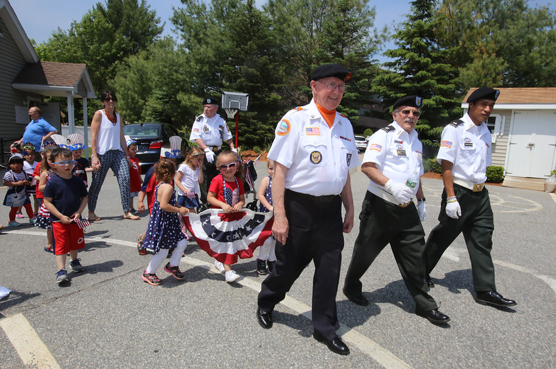 Annual Memorial Day parade at Building Blocks Preschool & Kindergarten. Leading the parade from left, Dave Laferriere of Vietnam Veterans of Greater Lowell, and Normand Diguere and Sam Thongsouvanh of VFW Post 662. All are from Lowell. (SUN/Julia Malakie)