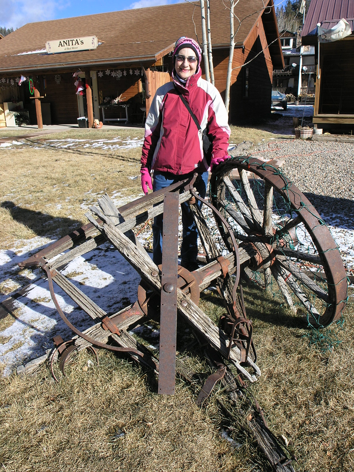 Betty Nelson posing next to a cart that has seen better days yet has been decorated with Christmas lights.