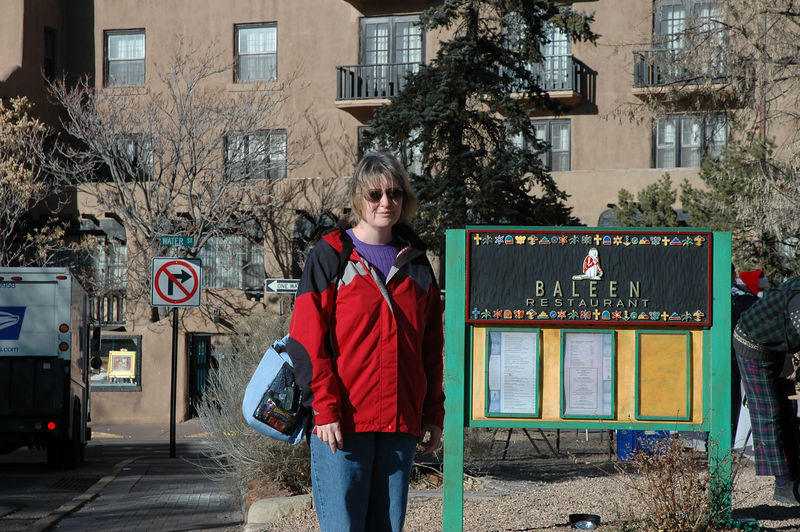 Susan posing near a restaurant sign a block or two from the Plaza