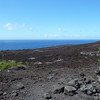 Another view of the most recent lava flow - dark, coarse grained rubble and splintered rock plungeing straight into the sea.