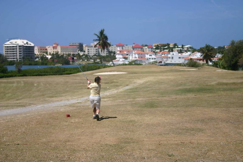 Having played there in 2004 we were not taken aback by the quality of the course.  But we played several holes with an American fellow who had arrived on a cruise ship which was stopped in Saint Martin for the day.  His choice of activity was golf or deep sea fishing.   The prior day his ship had been in Saint Thomas (Virgin Islands) and he had played golf on a wonderfully green, lush course.   He had expected the same in Saint Martin and felt ripped off - especially because with club and shoe rentals and power cart it cost him $148 U.S. to play.  I sympathized with him.  The course was not worth more than $25 to play.  But there is only one course on the island and so you take what you can get.   This is Francine hitting a good shot to the par three number four.