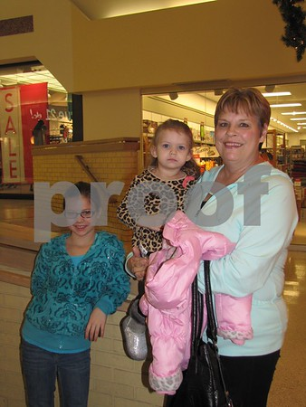 Kaylyne and Brooklyn Gililand with grandma Jayne Wiese wait for Santa to arrive at the Crossroads Mall.